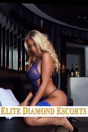 Beautiful blonde Maya kneels down down on a bed and wears blue lingerie and stocking set