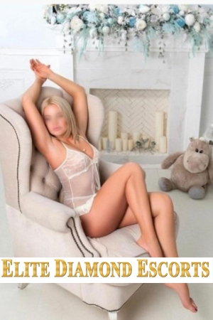 Ruby poses in a comfy chair with her arms above her head and shows off her white babydoll lingerie
