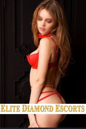 Red haired escort Adelle poses in a red bra and thong