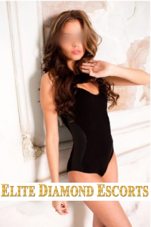 Sherwood escort Daisy leans against a wall in a black one piece whilst holding back her hair